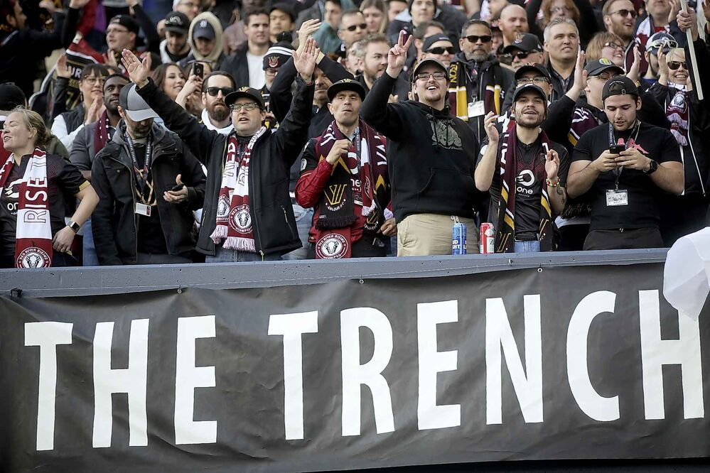 Fans in The Trench section of Investors Group Field celebrate after Valour FC's Micheal Petrasso scores the team's first goal at home, on a penalty kick, against FC Edmonton.<br>