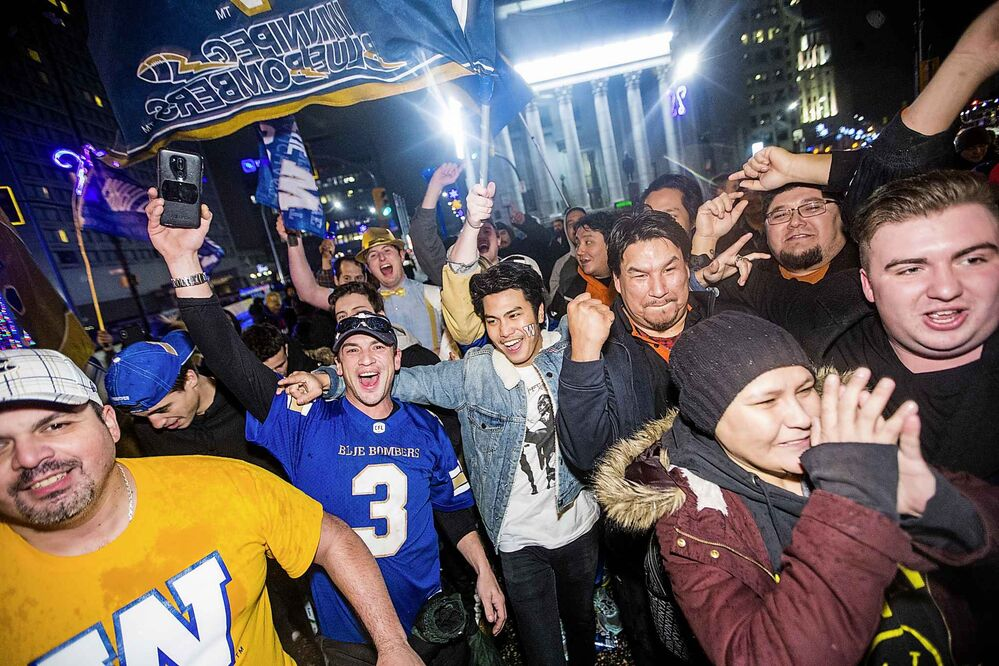 Bombers fans celebrate the Grey Cup win at Portage and Main in Winnipeg on Sunday. (Mikaela MacKenzie / Winnipeg Free Press) -