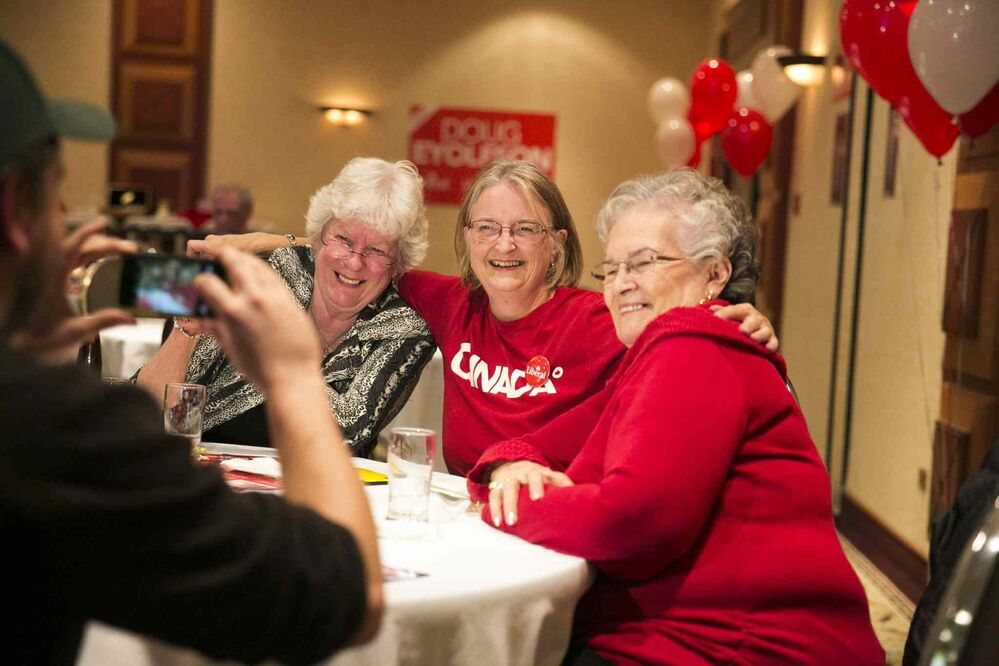Liberal supporters Barb King (left), Margaret Semple, and Jeannette Metcalfe a celebrate Doug Eyolfson's win at a Holiday Inn in Winnipeg on Monday, Oct. 19, 2015.  - Mikaela MacKenzie/Winnipeg Free Press