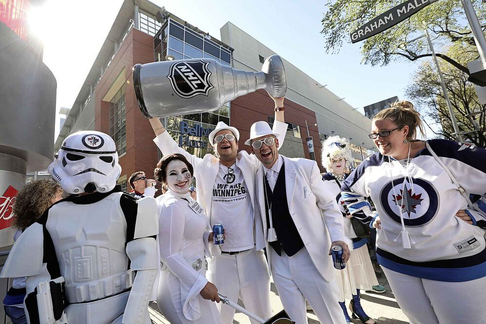 RUTH BONNEVILLE / WINNIPEG FREE PRESS<br>Brandon Klimenko (with friend Jeff Pinchin — both wearing white hats) hoists a fake Stanley Cup on Donald Street at Graham Avenue during the Whiteout street party before the start of Game 1 of the Western Conference final between the Winnipeg Jets and the Las Vegas Golden Knights in Winnipeg, Saturday, May 12, 2018. Klimenko hopes the Jets will win the real one.<br>