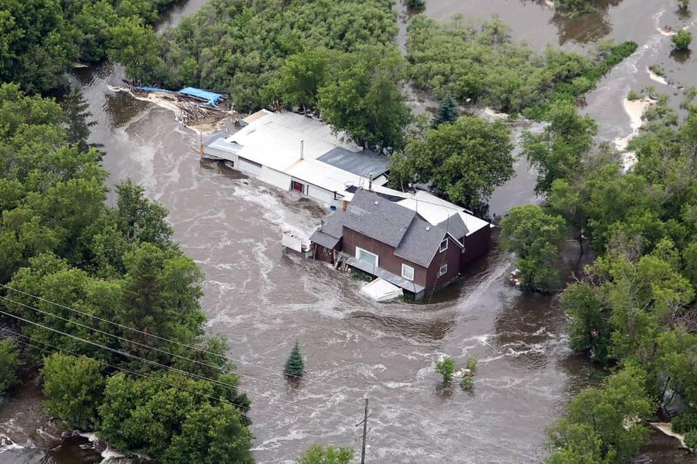 A home bordering the Little Saskatchewan River just west of the Rivers Reservoir spillway is surrounded by flood water on Monday after heavy downpours Sunday evening into overnight caused widespread flooding. (Tim Smith/The Brandon Sun)