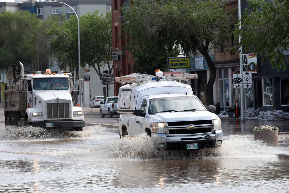 Vehicles pass through flood water on Main Street in Minnedosa on Monday after heavy downpours Sunday evening into overnight caused widespread flooding. The swollen Little Saskatchewan River overflowed into downtown Minnedosa flooding several businesses and residences. (Tim Smith/The Brandon Sun)