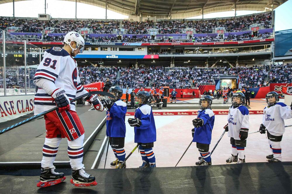 The Winnipeg Jets' Alexander Burmistrov (91) greets young players waiting to play an intermission game as he leaves the ice during the Heritage Classic game against the Edmonton Oilers at Investors Group Field.