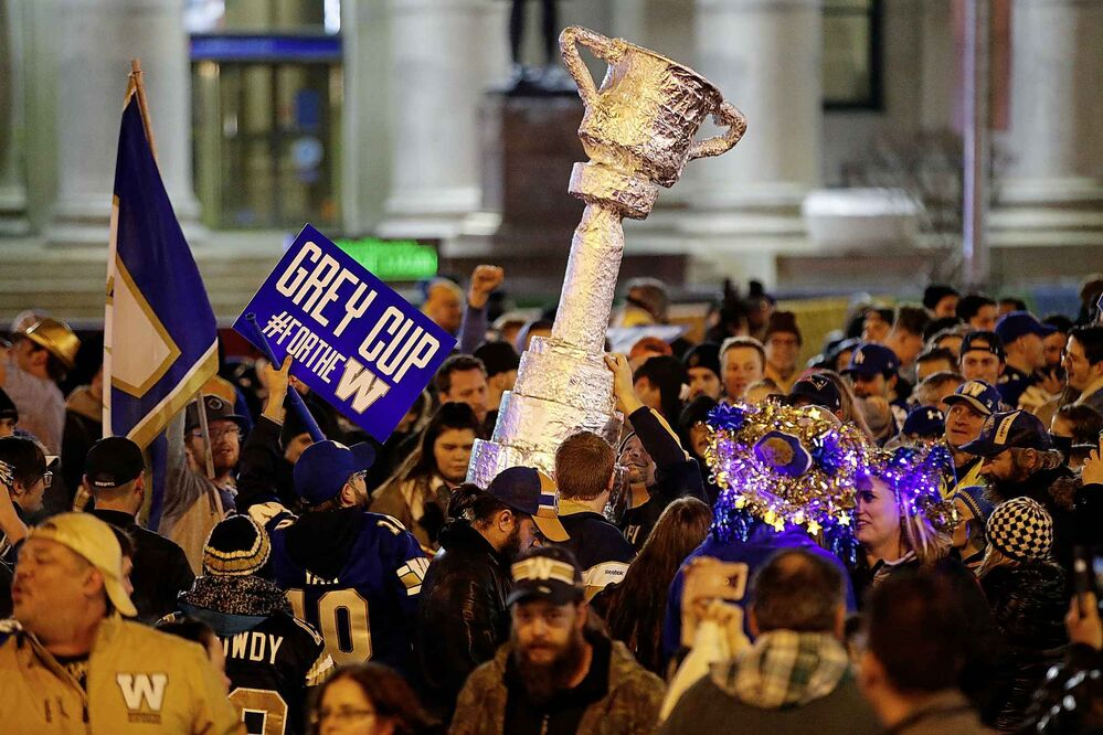 Winnipeg Blue Bomber fans celebrate winning the 107th Grey Cup over the Hamilton Tiger Cats at the intersection of Portage and Main in Winnipeg. (John Woods / Canadian Press) - CP