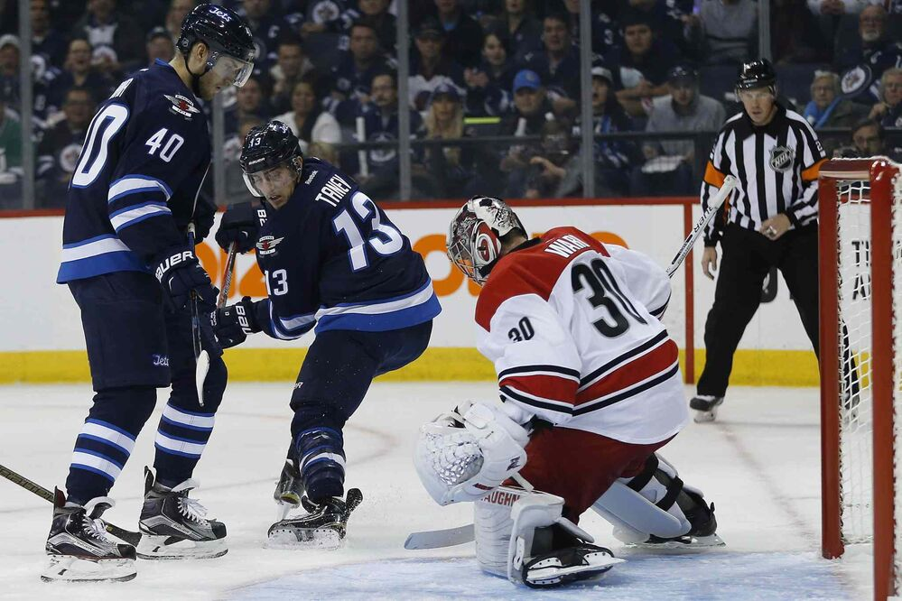 Carolina Hurricanes goaltender Cam Ward (30) saves the backhander from Winnipeg Jets' Brandon Tanev (13) as Joel Armia (40) looks for a rebound during second period NHL action in Winnipeg on Thursday, October 13, 2016.  - JOHN WOODS / THE CANADIAN PRESS