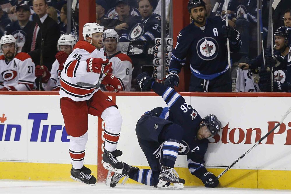 Winnipeg Jets' Blake Wheeler (26) gets checked by Carolina Hurricanes' Ron Hainsey (65) during second period NHL action in Winnipeg on Thursday, October 13, 2016. - JOHN WOODS / THE CANADIAN PRESS