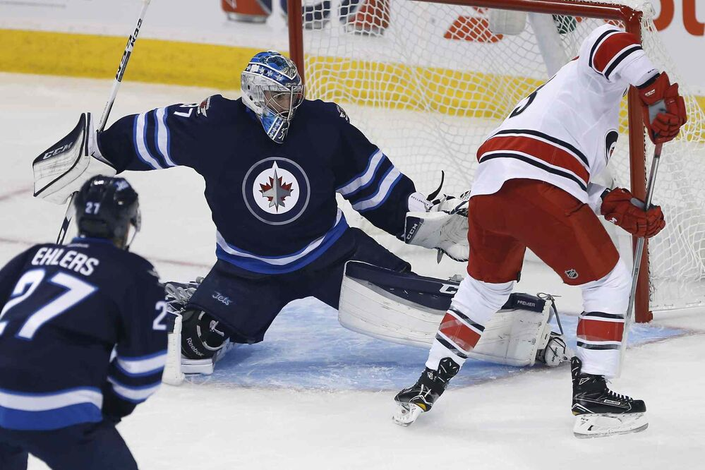 Carolina Hurricanes' Jeff Skinner (53) scores on Winnipeg Jets goaltender Connor Hellebuyck (37) as Nikolaj Ehlers (27) defends during first period NHL action in Winnipeg on Thursday, October 13, 2016. - JOHN WOODS / THE CANADIAN PRESS