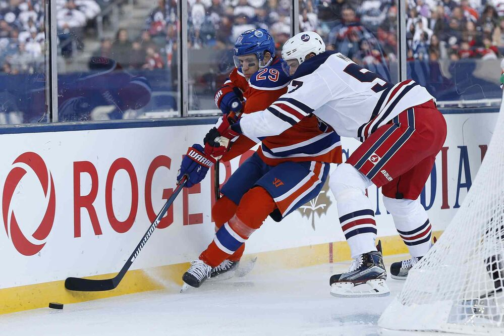 Edmonton Oilers' Leon Draisaitl (29) and Winnipeg Jets' Tyler Myers (57) go for the puck in Jets' territory during first period of the NHL Heritage Classic Sunday.  - JOHN WOODS / The Canadian Press