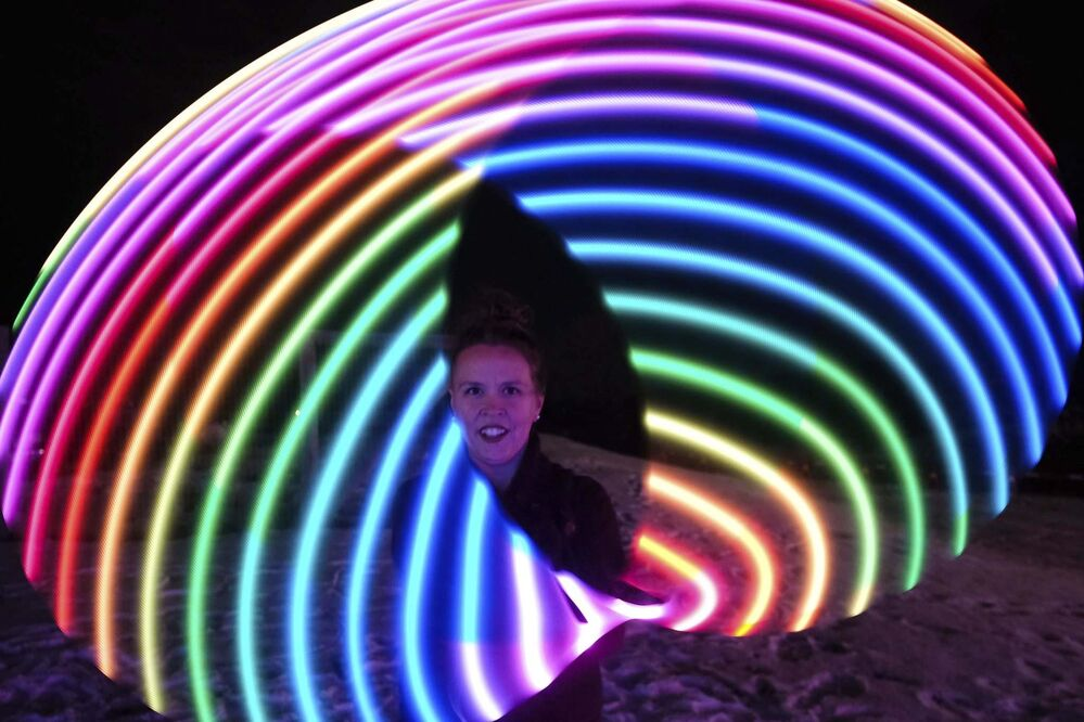 Hoopist Karrie Blackburn shows off her skills with a lit up hula-hoop at the Zoo Lights Festival. (Daniel Crump / Winnipeg Free Press)