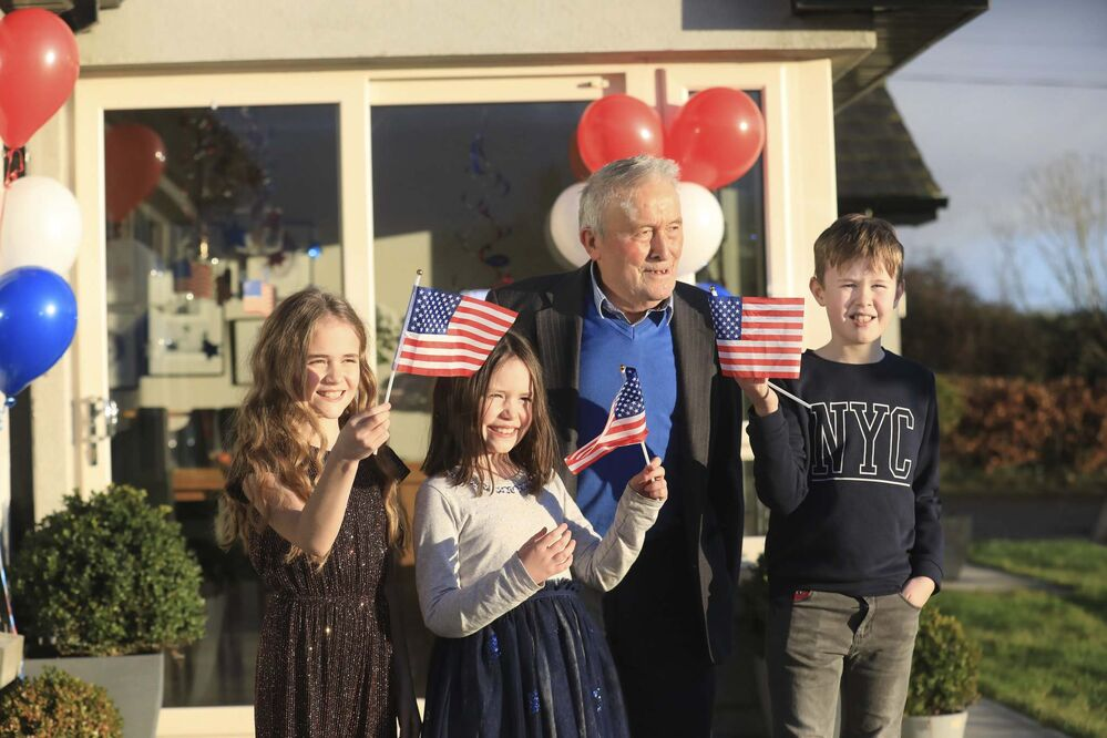 Peter Morrison / The Associated Press<br>Joe Biden's cousin Brendan Blewitt with his grandchildren Emily, Lauren and Darragh wave their U.S. flags to the media from their home in Knockmore, near the town of Ballina in Ireland on Wednesday.<br>