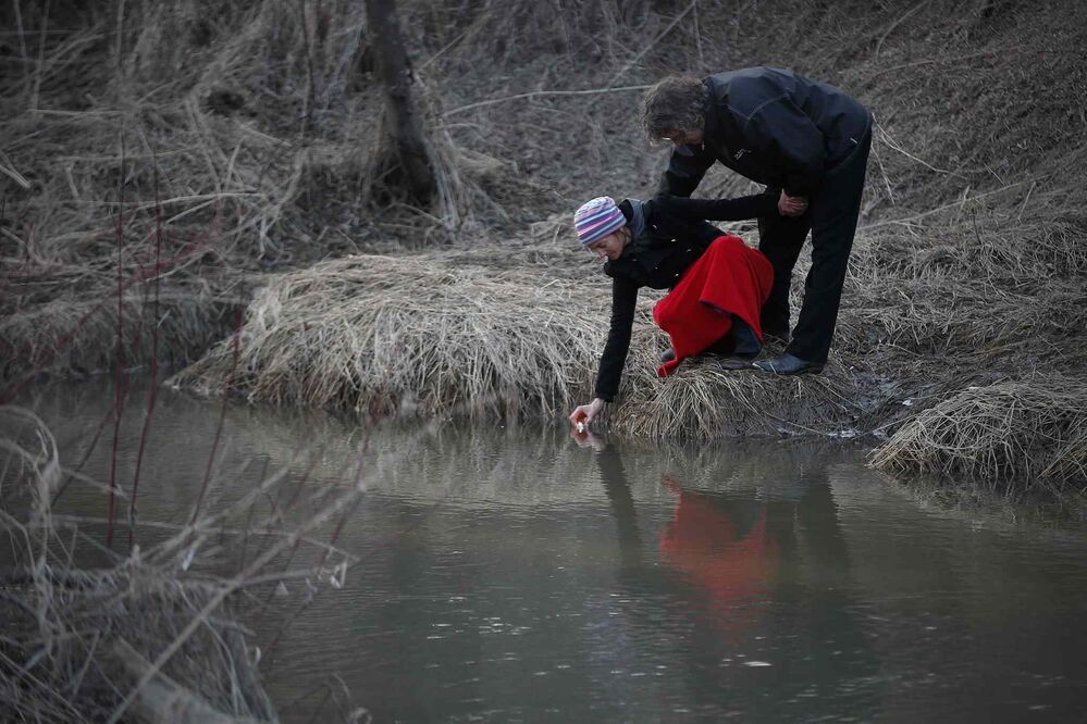 A couple floats a candle in a creek after a vigil for two-year-old Chase Martens whose body was discovered in Pine Creek about half a kilometre from his home just north of Austin, Manitoba. March 26, 2016.  -