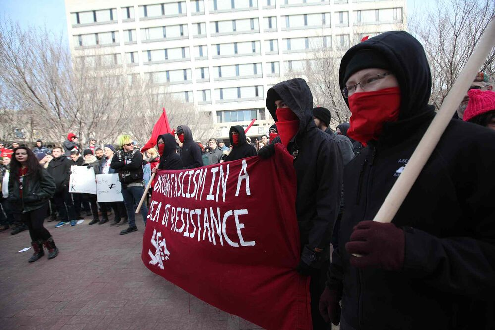 "Part of the group of protesters at Winnipeg's City Hall held a banner reading ""Drown Fascism in a Sea of Resistance"". The members wore black hoods and red face masks. - RUTH BONNEVILLE / WINNIPEG FREE PRESS"