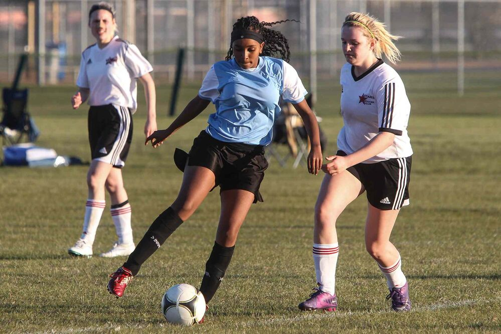 """The Immigrant and Refugee Community Organization of Manitoba """"IRCOM"""" Cobras under-16 girls soccer team playing the West St. Paul Stars U-16 team Wednesday evening. Nasra from the IRCOM Cobras moves the ball past a player with the West St. Paul Stars. May 20, 2015 -  (MIKE DEAL / WINNIPEG FREE PRESS) - MIKE DEAL / WINNIPEG FREE PRESS"""