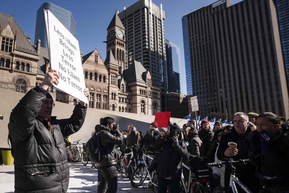 Protesters gather at Toronto City Hall. - CHRISTOPHER KATSAROV / THE CANADIAN PRESS