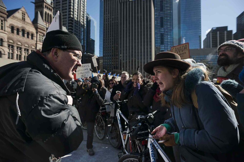 Protesters with opposing views argue at Toronto City Hall. - CHRISTOPHER KATSAROV / THE CANADIAN PRESS
