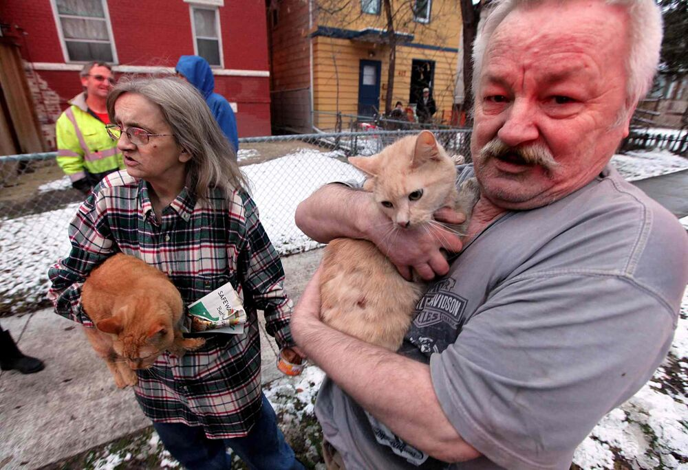 Nicole and Aaron Wolf cling to two of their five cats after they escaped a burning Maryland apartment building.  November 30, 2016 -