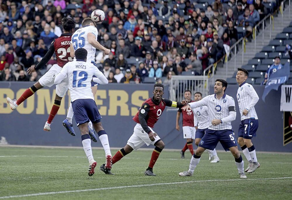 Valour FC's Ali Musse takes to the air against FC Edmonton's Amer Didic for the ball.<br>