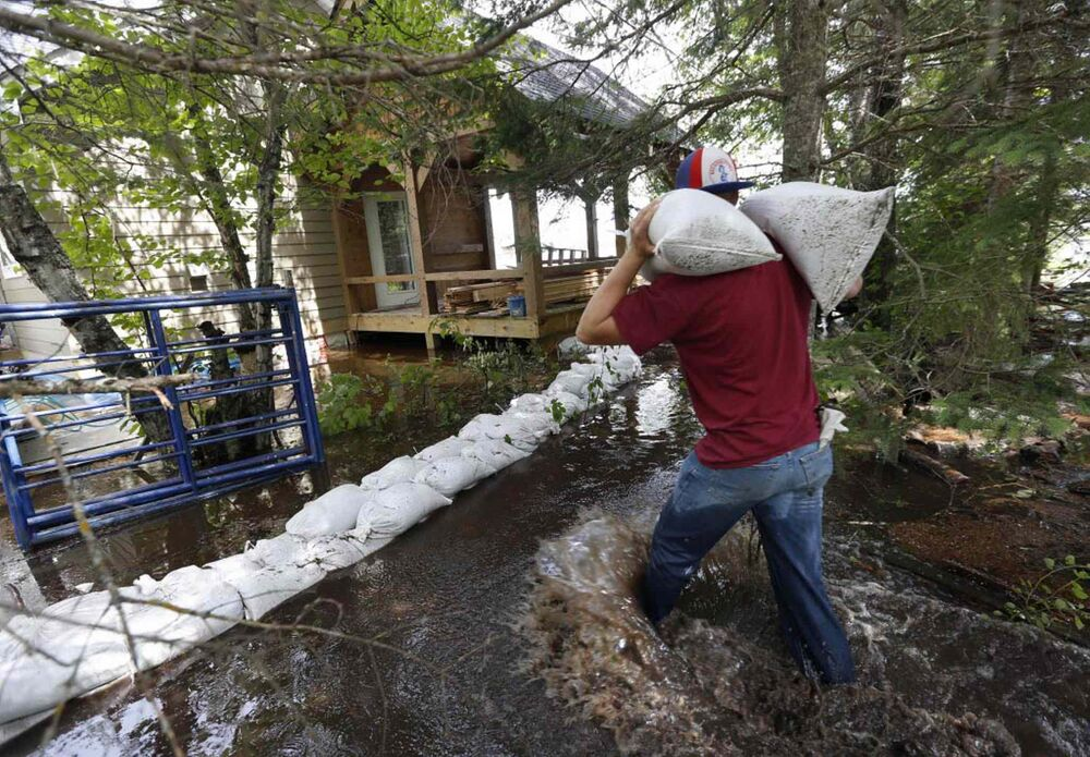 Park staff help sandbag Jason Fehr's cottage along Caddy Lake. June 27, 2016. -