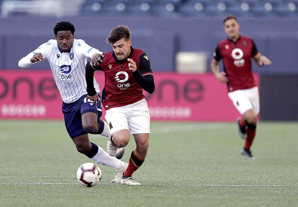 FC Edmonton Kareem Moses (left) and Valour FC Micheal Petrasso (centre) battle for the ball.<br>