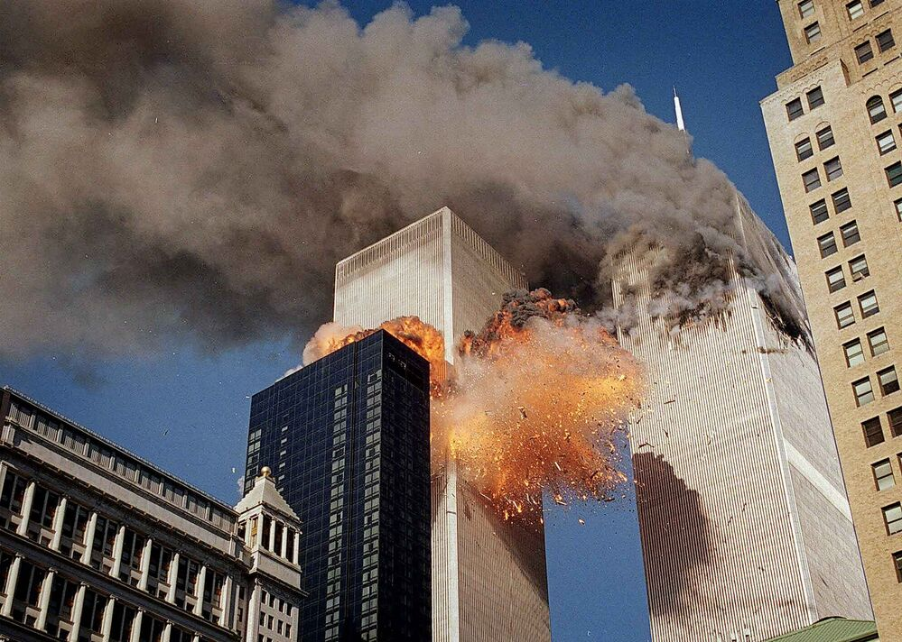 Smoke billows from one of the towers of the World Trade Center as flames and debris explode from the second tower, Tuesday, Sept. 11, 2001. (AP Photo/Chao Soi Cheong) - =