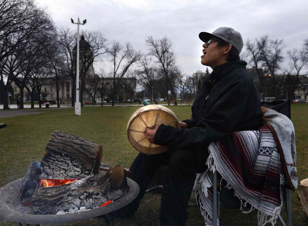Shane Flett, 17, from the Island Lake First Nation sings a song to strengthen his spirits after spending a cold night camped in Memorial Park across from the Manitoba Legislative Building. He wants to bring awareness to the importance of Indigenous self governance and wants others to join him in the park. He also hopes to meet with provincial leaders. November 16, 2016. -