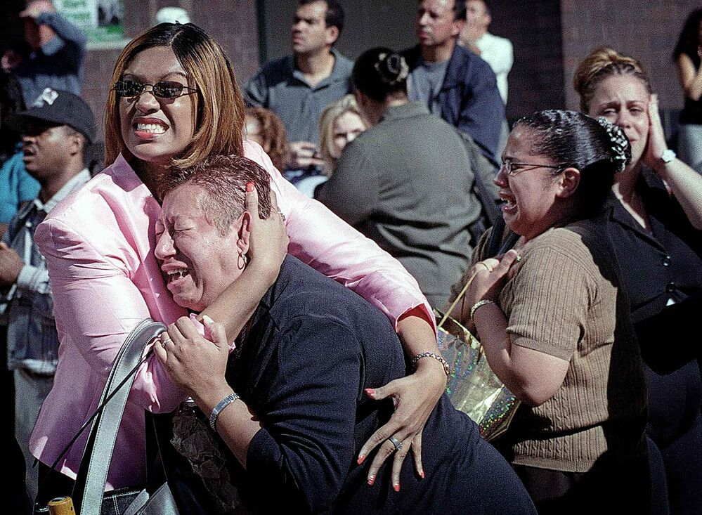 Two women hold each other as they watch the World Trade Center burn in New York Tuesday, Sept. 11, 2001. (AP Photo/Ernesto Mora) -
