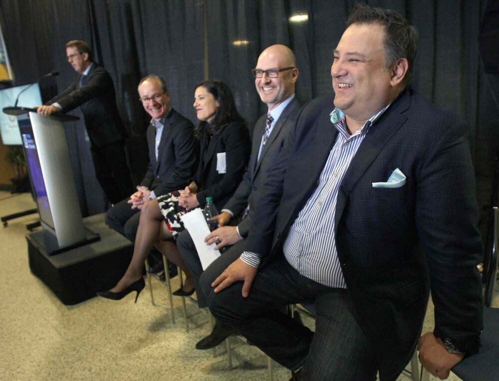 Tom Gaglardi, right, Chairman and CEO of Sutton Place Hotels laughs as Mark Chipman introduces him at the news conference. - JOE BRYKSA / WINNIPEG FREE PRESS
