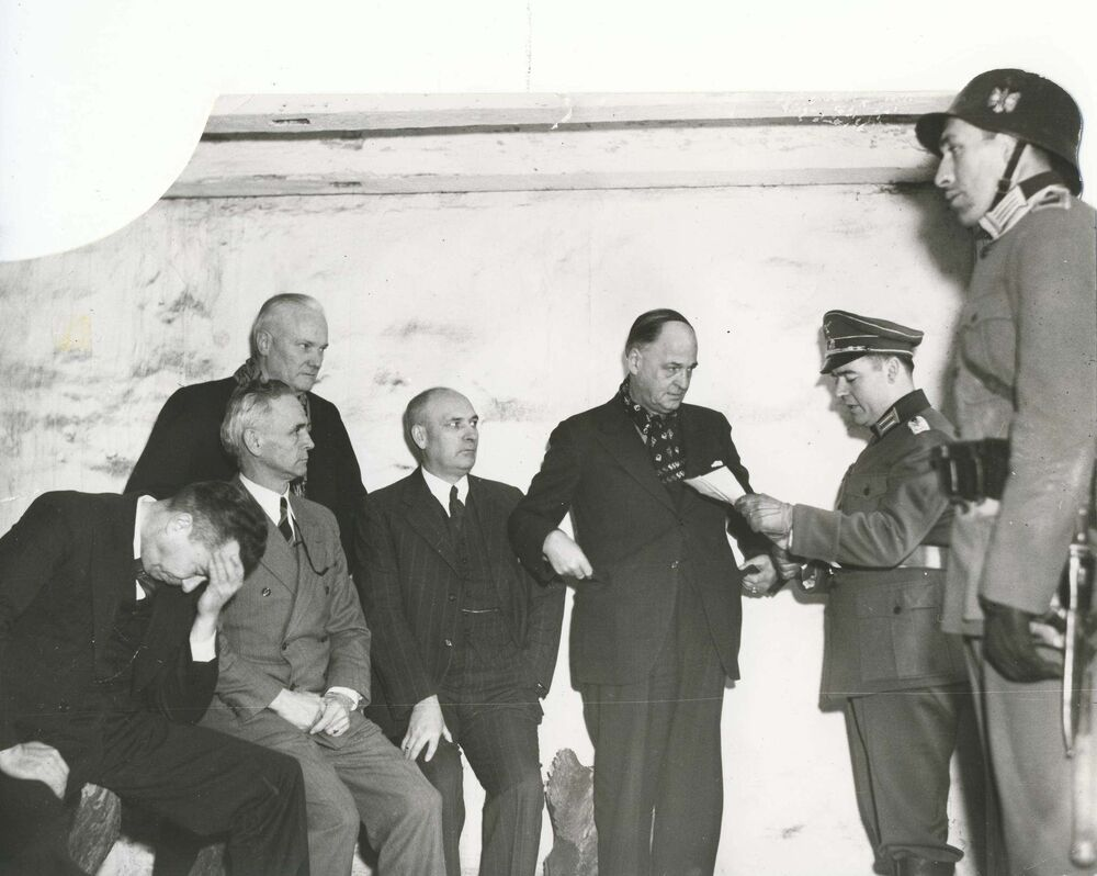 A Nazi officer reads charges to provincial cabinet minister Errick Willis (from left), premier John Bracken., cabinet minister J. S. McDiarmid, cabinet minister James McLeneghan and Winnipeg mayor John Queen after confining them to the dungeon.  - Winnipeg Free Press Archives