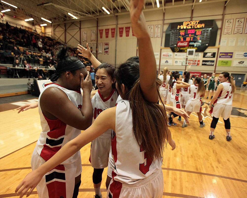 Sisler Spartan Kyanna Giles (11) weeps as she is embraced by team mates Raizel Guinto (6), Kyia Giles (7) and Kiara Rongavilla (3) after the team won the MHSAA Basketball Championship at Investor's Group Athletic Centre. March 21, 2016 -