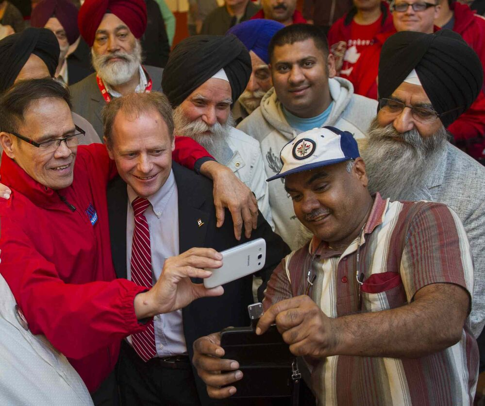 Incumbent Liberal Kevin Lamoureux (red tie) joins supporters at the Punjab Banquet Hall in his Winnipeg North riding Monday. - DAVID LIPNOWSKI / WINNIPEG FREE PRESS