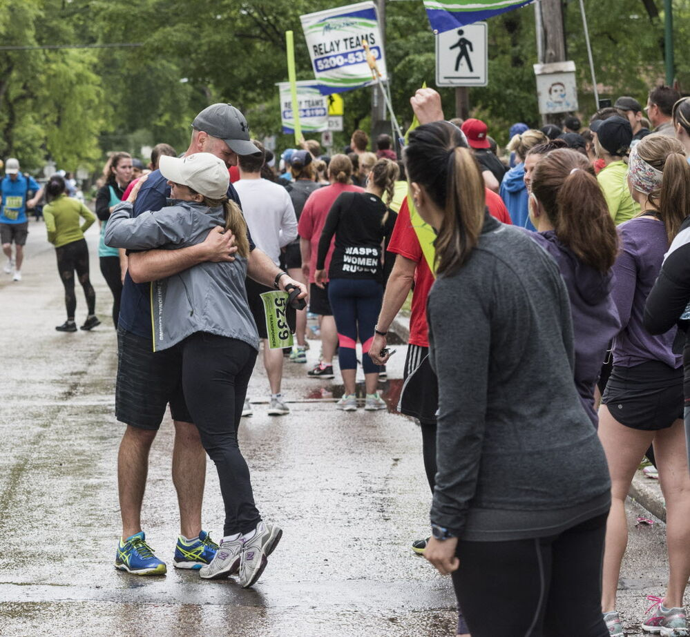Manitoba Marathon relay participants Miles Macdonell gets a hug from National Leasing co-worker Alfie Imbrogno as they hand off during their run on Wolseley Avenue Sunday June 18, 2017. - DAVID LIPNOWSKI / WINNIPEG FREE PRESS