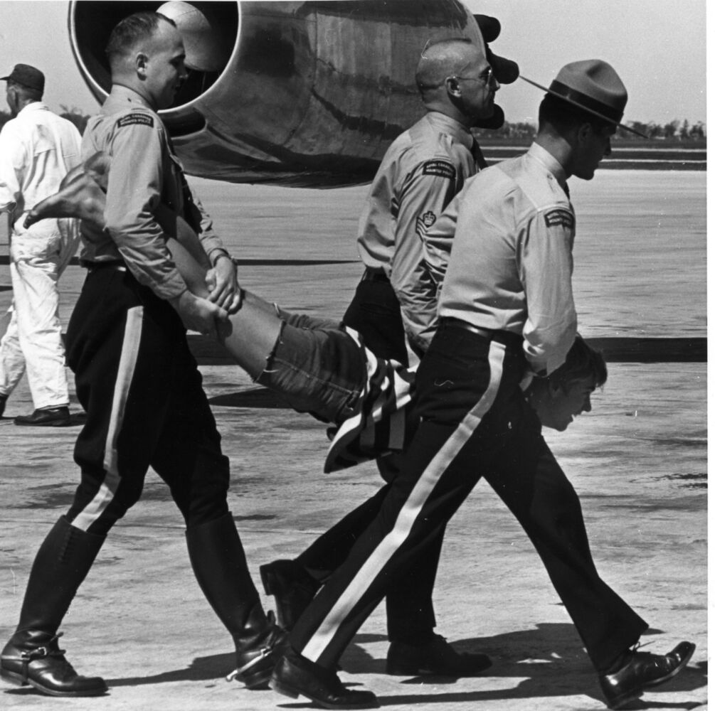 Bruce Decker, 17, is carried away by RCMP after making a run for the stairs where the Beatles had just greeted fans at Winnipeg International Airport on Aug. 18, 1964. (Dave Bonner photo)