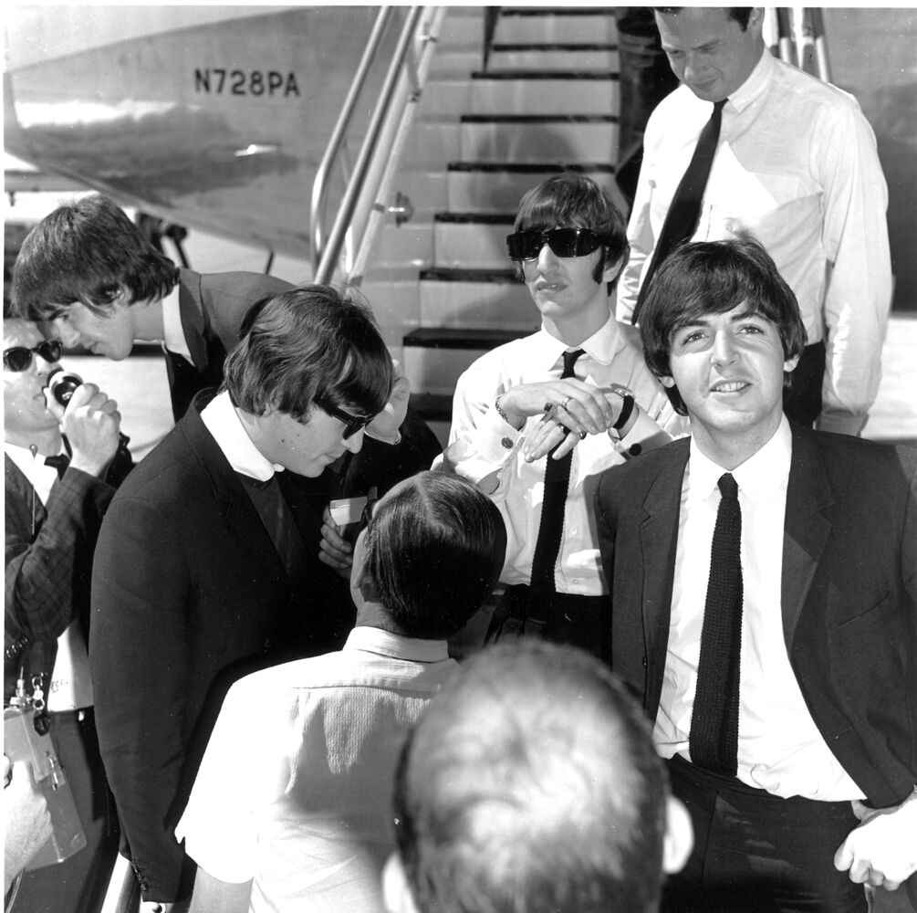 The Beatles are interviewed by journalists after landing at Winnipeg International Airport.