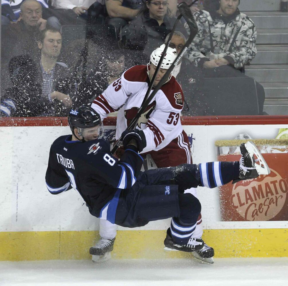 Winnipeg Jets' Jacob Trouba (8) is knocked off his feet by Phoenix Coyotes Derek Morris (53) during the third period.