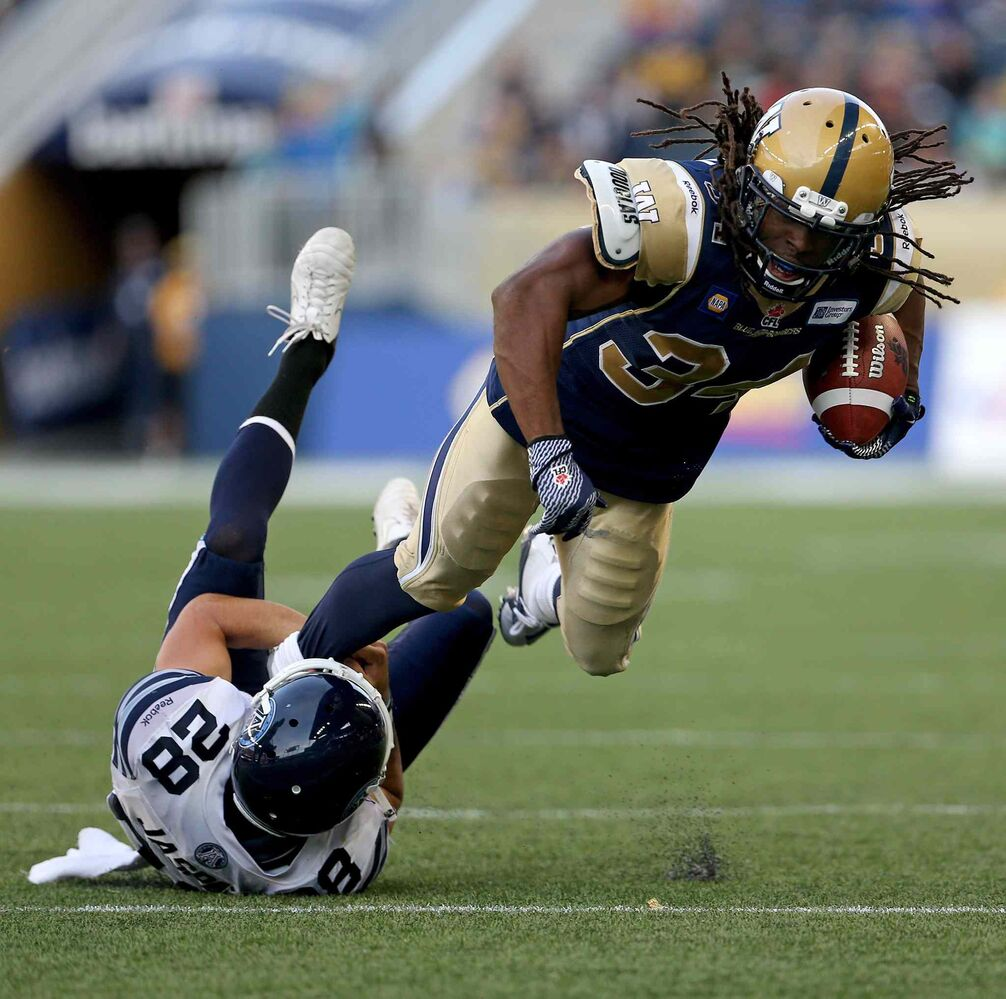 Argonauts defender Josh Jasper brings down Bombers running back/kick returner Paris Cotton during the first half of pre-season CFL football action at Investors Group Field.