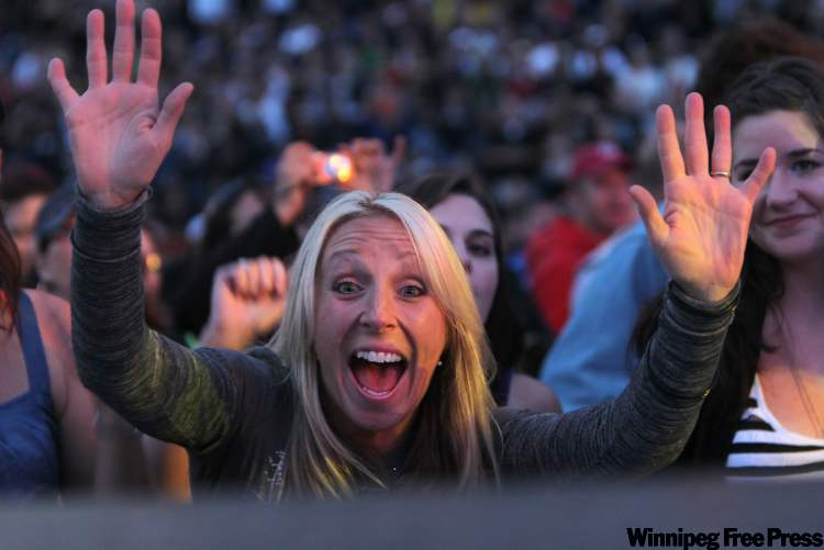 Front row fans scream as they lean into the stage at the Bon Jovi concert at Canad Inns Stadium Saturday night.