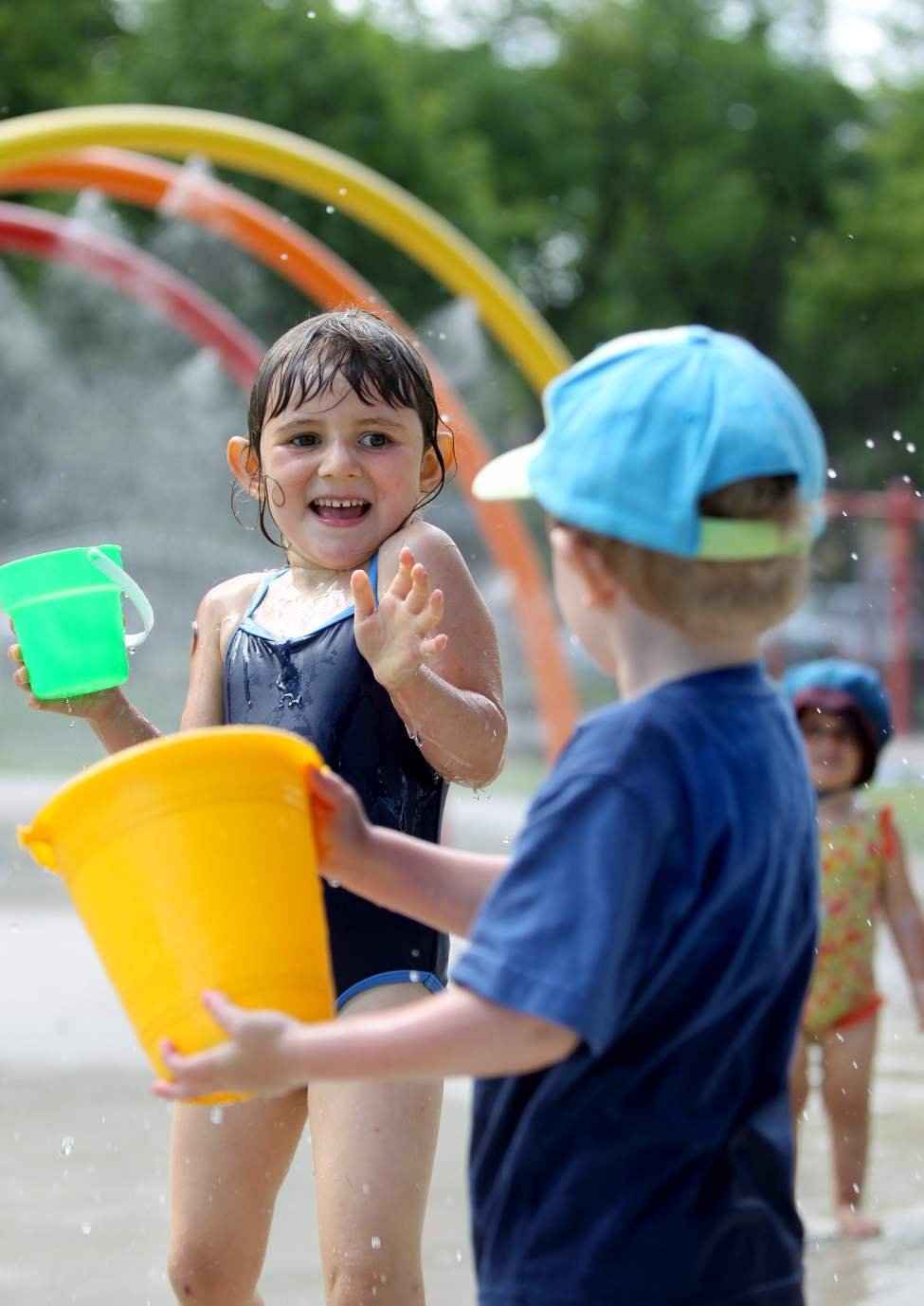 Four year old Leah Noel winces as her cousin Jean-Michel Gendron, 3, sprays her with water while playing at the Provencher Park Spray Pad.  July 5 2010