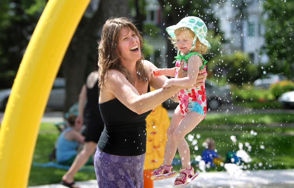 Four year old Leah Noel winces as her cousin Jean-Michel Gendron, 3, sprays her with water while playing at the Provencher Park Spray Pad. July 5 2010 (RUTH BONNEVILLE / WINNIPEG FREE PRESS)