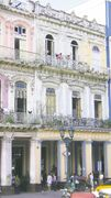 Havana residents enjoy an afternoon chat on their balconies across from Parque Central. The park is a hub of activity in downtown Havana where the Habana Bus Tour stops to transport tourists and locals around the city of over two million people.