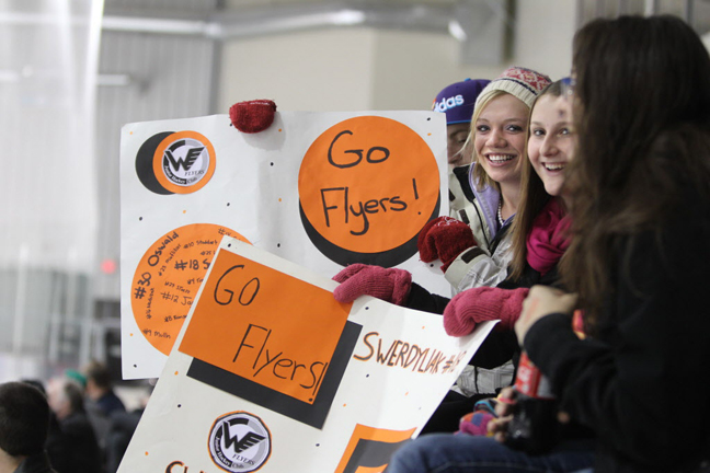 Annette Tourand  (hat) and her friend Jillian Leclerc hold up their homemade signs as they cheer for the Winkler Flyers during thier game against the Waywayseecappo Wolverines during at The  Old Dutch MJHL Showcase  Tournament  at IcePlex Arena Saturday. The Waywayseecappo Wolverines went on to win the game 4 -3 in a shootout. (Ruth Bonneville / Winnipeg Free Press)