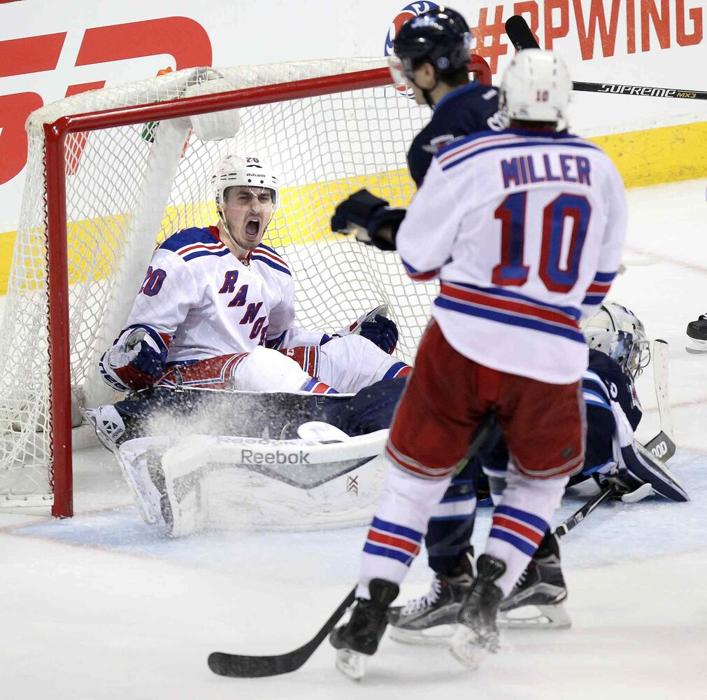New York Rangers Chris Kreider celebrates after scoring the game-winning goal Tuesday. He and the puck wound up in the net behind Ondrej Pavelec late in the third period. (Phil Hossack / Winnipeg Free Press)