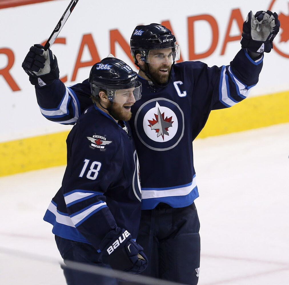 Winnipeg Jets' Bryan Little (18) and Andrew Ladd (16) celebrate after Little scored against the Dallas Stars during first period. (Trevor Hagan / The Canadian Press)