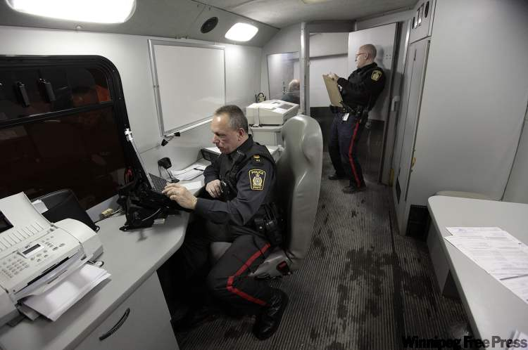 Sgt. Rick Zurba (left) and Sgt. Rob Riffel process an impaired-driving suspect who blew a 0.13 blood alcohol reading on the checkstop van's Datamaster machine. The legal limit is 0.08.