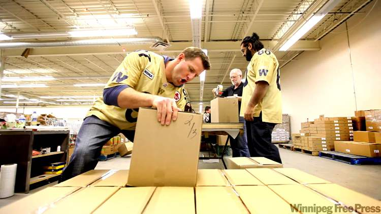 Blue Bombers defensive lineman Doug Brown hams it up as he tackles a hamper box at the Cheer Board warehouse. Offensive lineman Obby Khan (60) is taking his duties much more seriously.