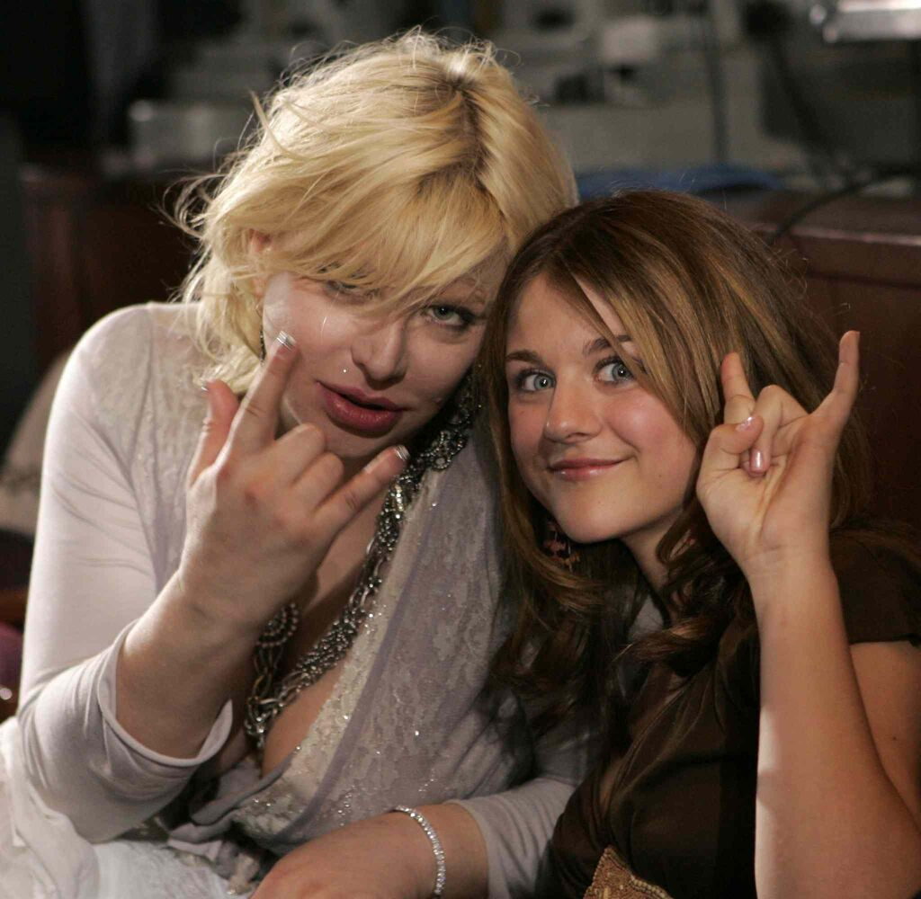 "Courtney Love, left, gestures with her daughter Frances Bean as they watch the ""American Idol"" live finale in Los Angeles in 2005.  (Kevork Djansezian / The Associated Press)"