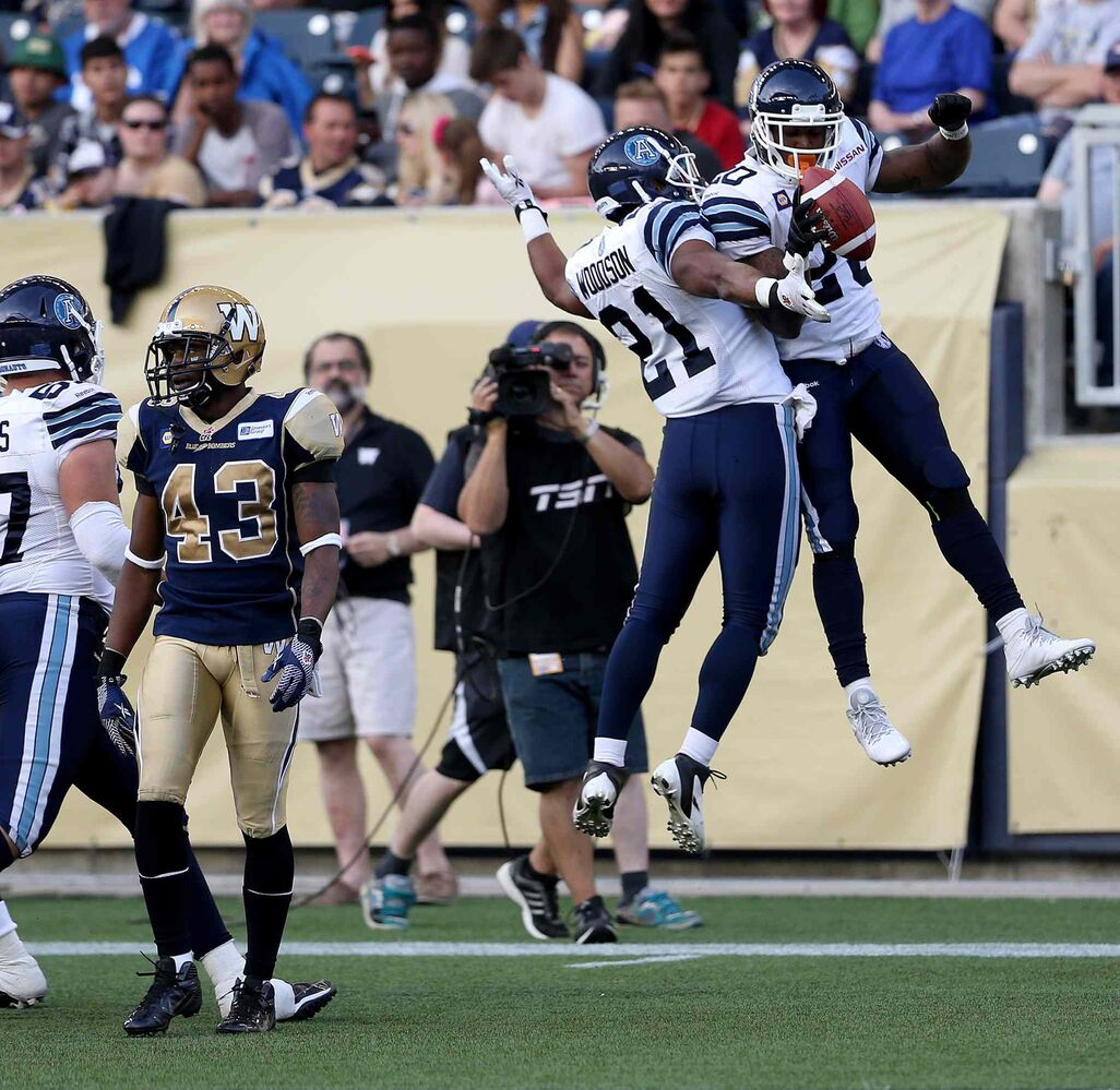 The Argos' Anthony Woodson (21) and Steve Slaton celebrate a first-half touchdown. (TREVOR HAGAN / THE CANADIAN PRESS)