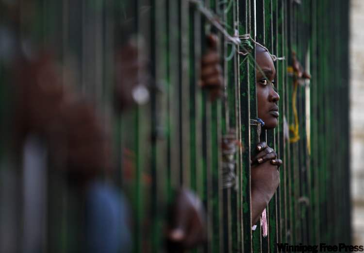 A woman peers through the bars of a fence while watching a food distribution operation in Port-au-Prince, Saturday, Feb. 6, 2010. After the Jan. 12 powerful earthquake ravaged much of Haiti's capital, attacks against women increased and women said gangs of men stole their food coupons used at distribution points in the outdoor camps, home to more than half a million earthquake survivors.