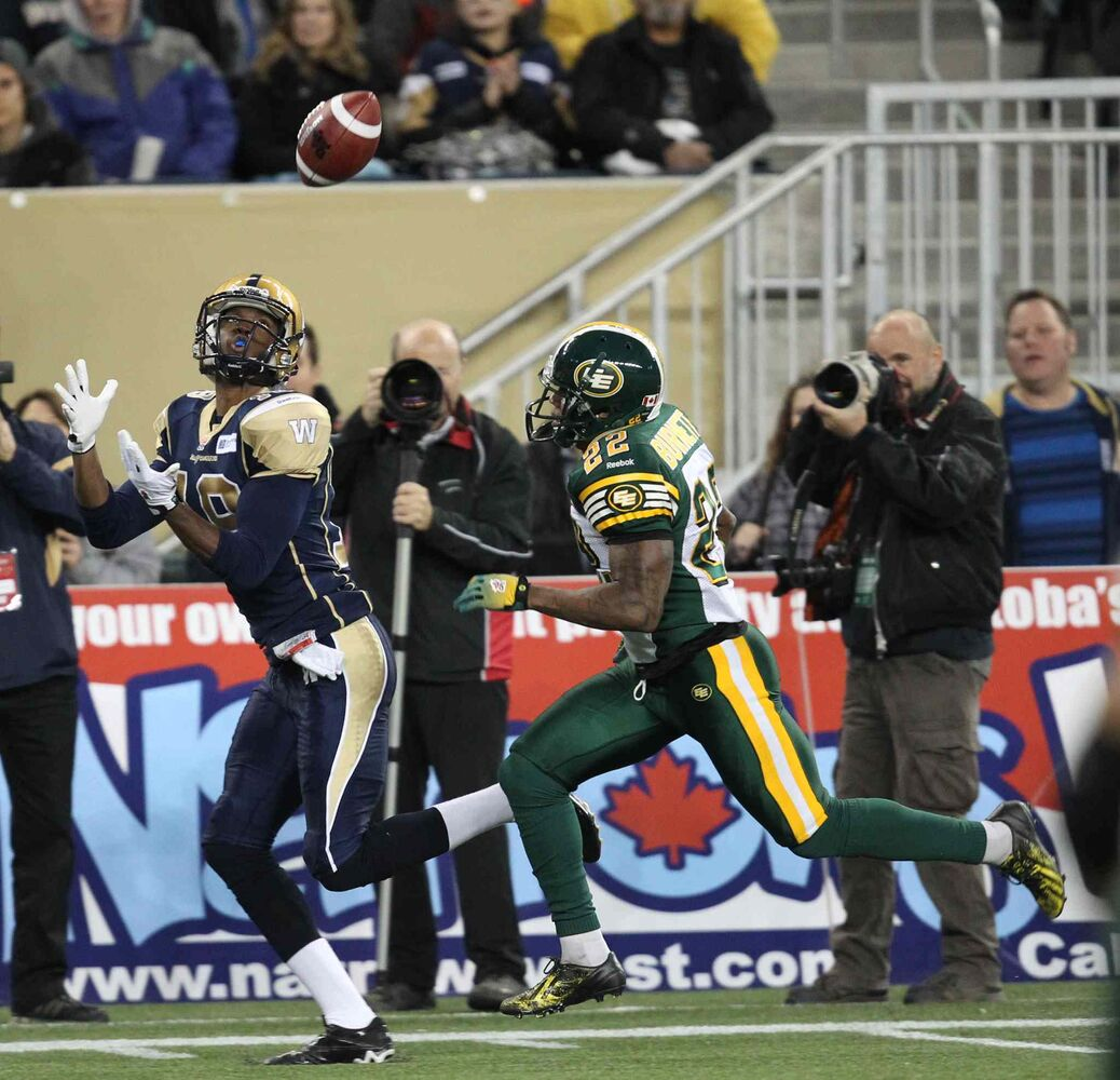 Winnipeg Blue Bombers Aaron Kelly makes a catch as Edmonton Eskimos Joe Burnett gives chase during the first half.