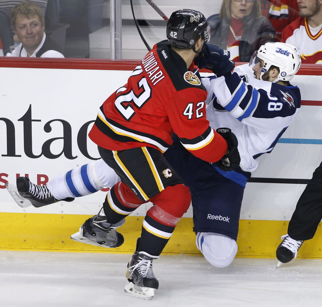 Winnipeg Jets' Eric O'Dell, right, takes a hit from Calgary Flames' Mark Cundari during the second period of Friday's game. (Larry MacDougal / The Canadian Press)