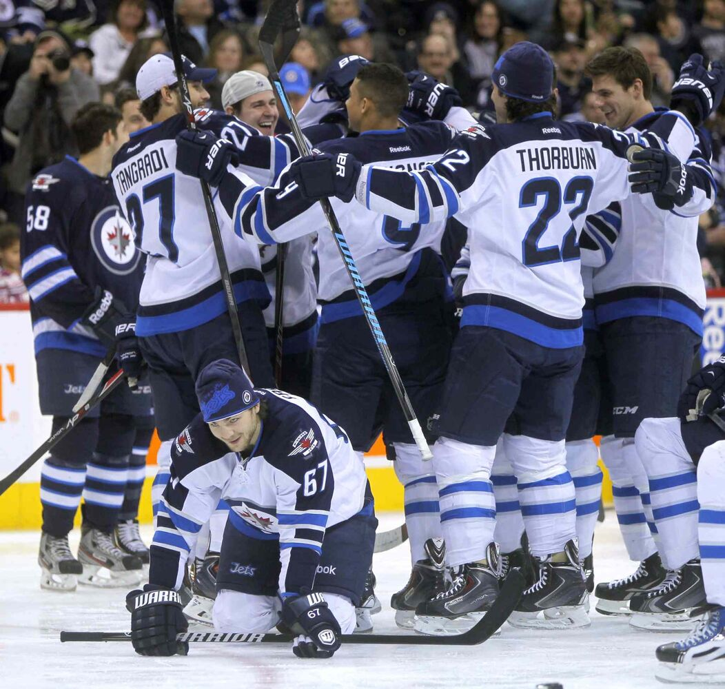 Team White celebrates a victory during the skills competition. It's unclear what Michael Frolik (bottom) is up to. (Boris Minkevich / Winnipeg Free Press)